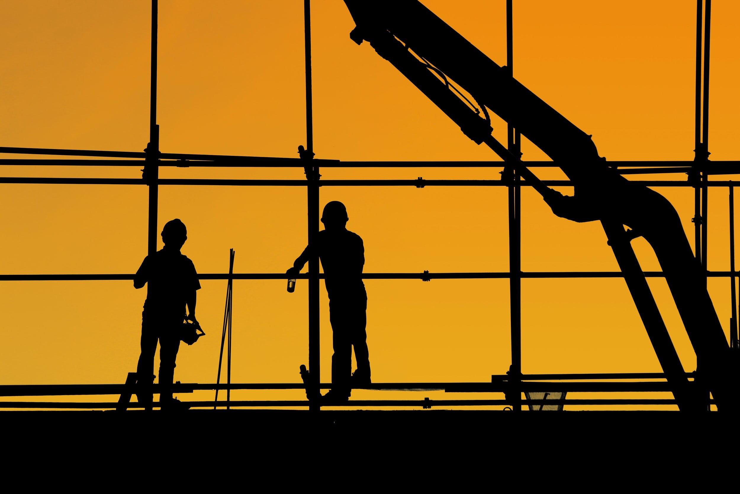 Image of workers against a orange sky
